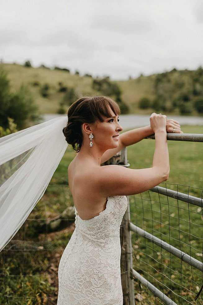 Bride leaning against fence with flowing veil